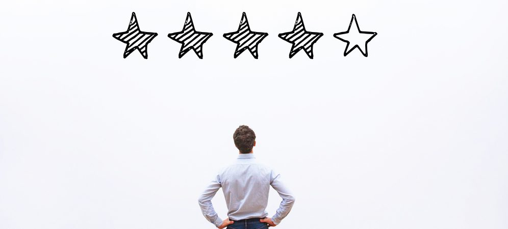 healthcare marketing - business man looking at wall with 4 out of 5 stars filled in