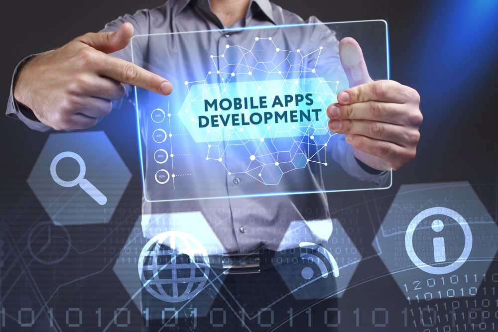 "business man holding holographic template labeled ""mobile apps development"""