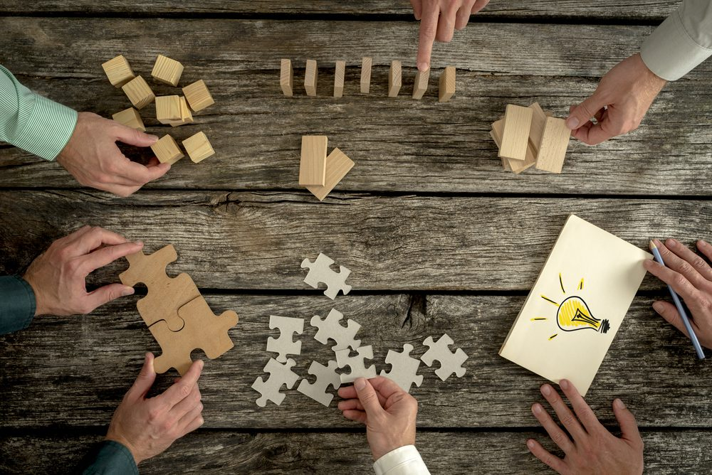 Puzzle pieces, dominos, and wooden blocks on wooden table