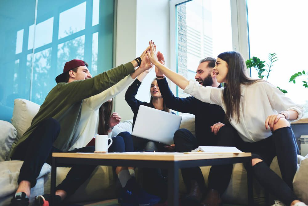 marketing team huddle in open work space celebrating with a group high-five
