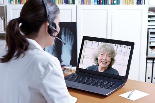 doctor teleconferencing with patient using laptop