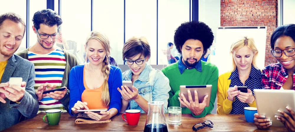 Many young people looking excitedly at financial services using tablets and mobile phones
