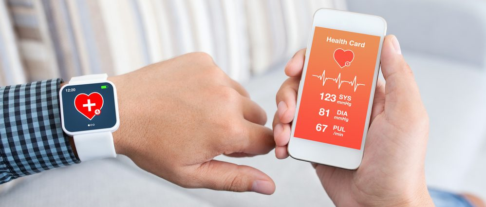 Patient wearing smart watch with vital metrics showing on smartphone screen