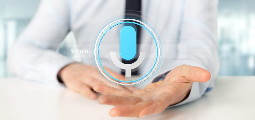 Healthcare professional with his palm facing app and a voice tech symbol hovering over his palm