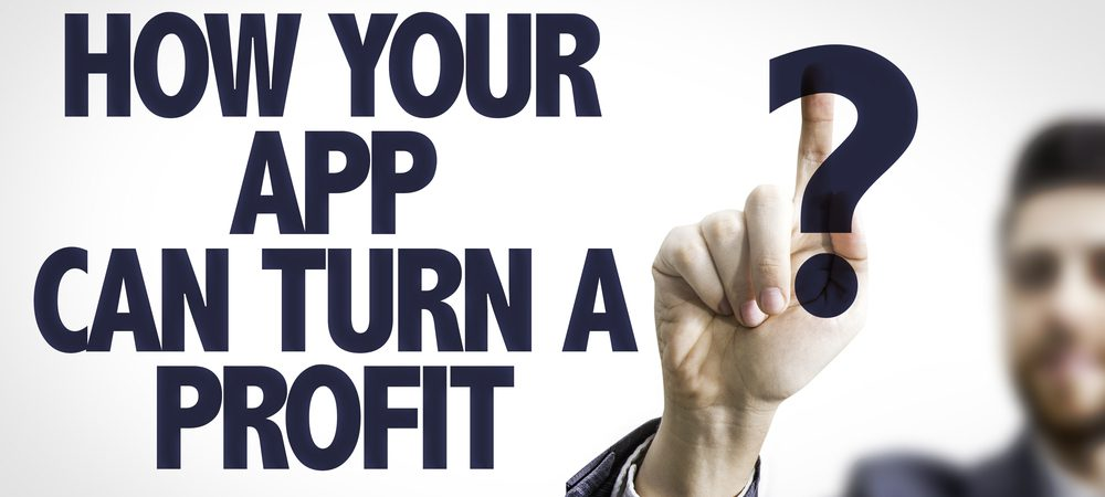 """Business man looking at a monitor displaying the question """"How your app can turn a profit?"""""""