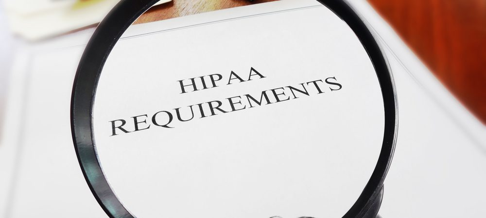 Magnifying glass hovering over a paper that reads Hipaa Requirements