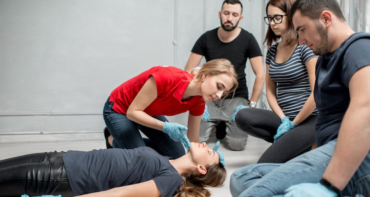 Female instructor administering first aid in front of students