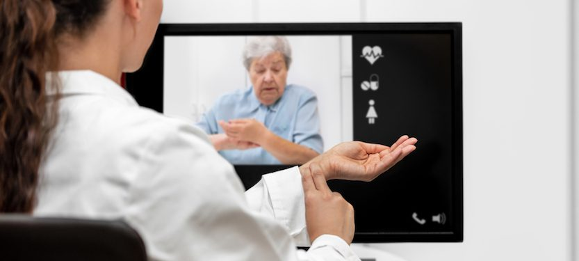 Doctor interacting with a patient via video display.