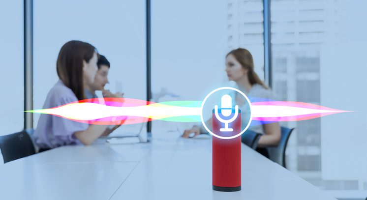 People having a conversation at a conference table that has a red smart speaker on it