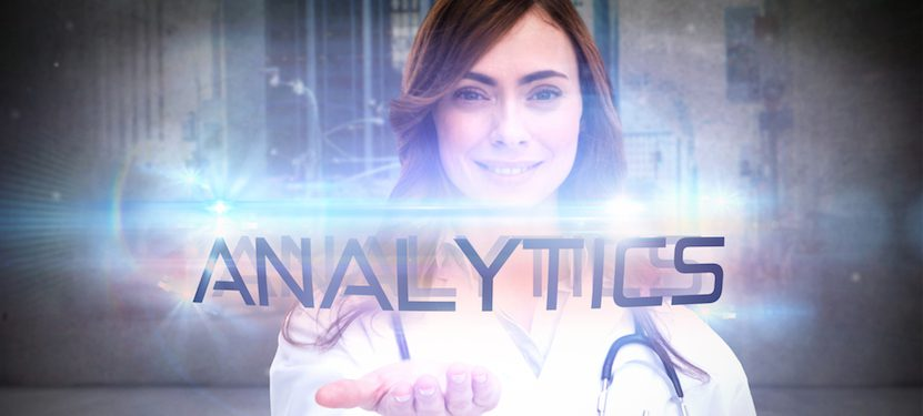 "A doctor holding the word ""Analytics"" in her hand."