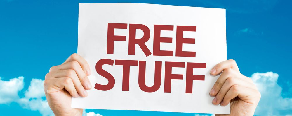 "Hands holding up a sign that says ""Free Stuff"" on it."