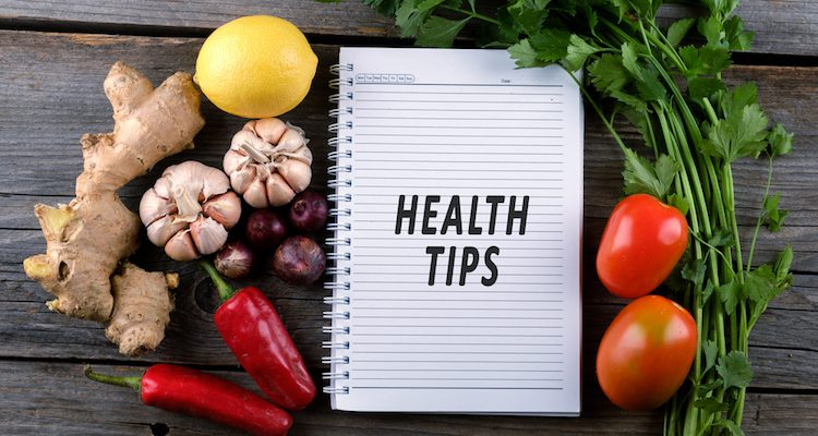 Paper journal with health tips on a table with fresh vegetables