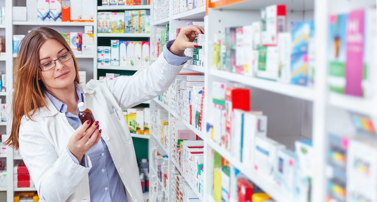 Female pharmacist examining bottles from pharmacy shelves