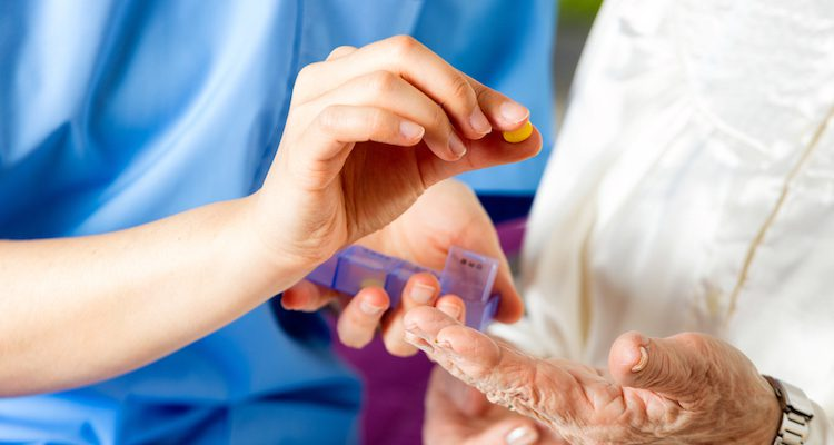 A nurse handing pills to an elderly patient