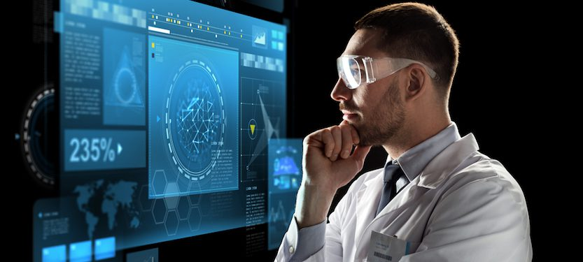 A physician looking at a screen of data.