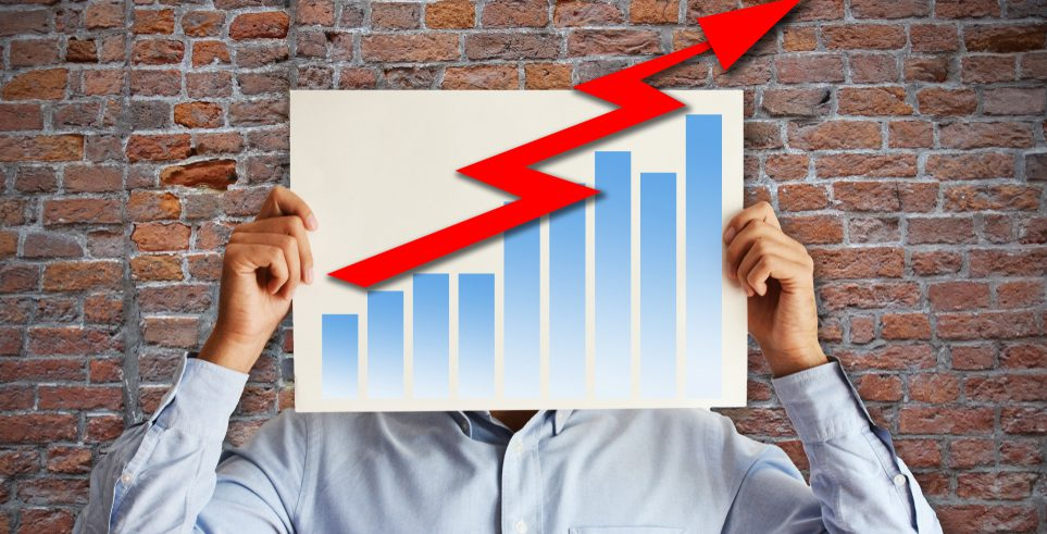 A man holding a bar graph in front of his face.