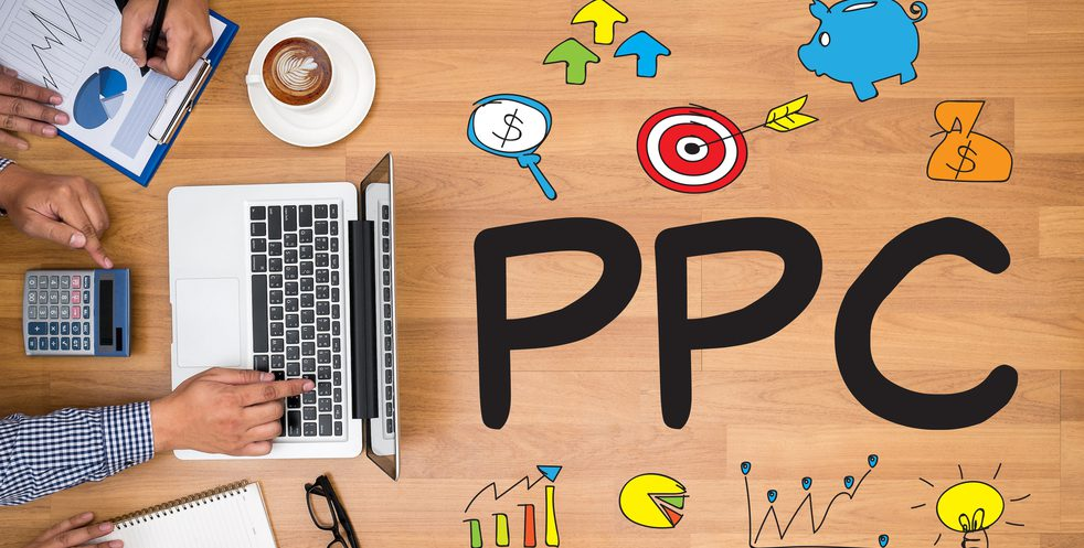 """People at a laptop with the letters spelling """"PPC"""" on the table."""