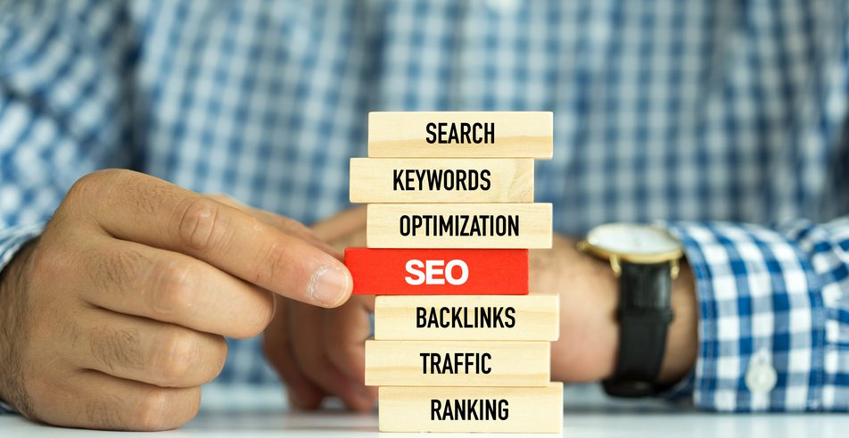 "A stack of blocks with the words ""Search"", ""Keywords"", ""Optimization"", ""SEO (Highlighted in Red)"", ""Backlinks"", ""Traffic"", and ""Ranking"" stacked in that order."