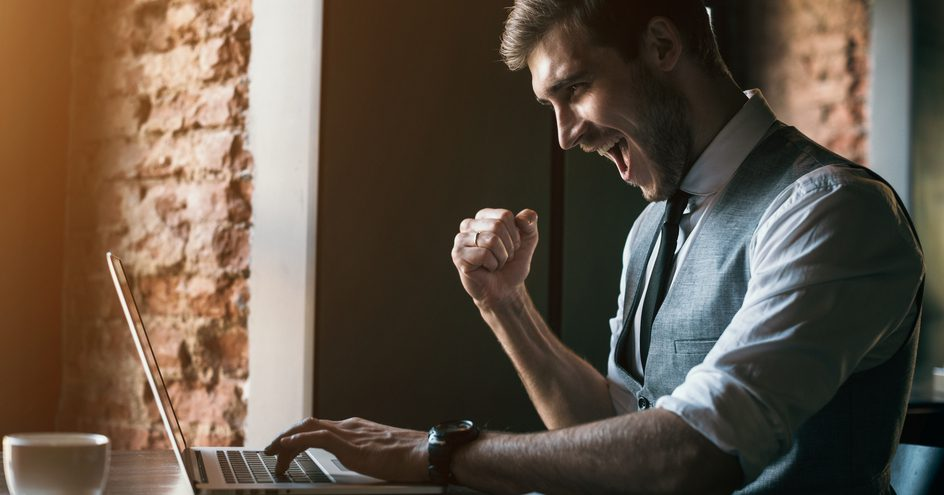 A man at a laptop fist pumping with a cheerful attitude.