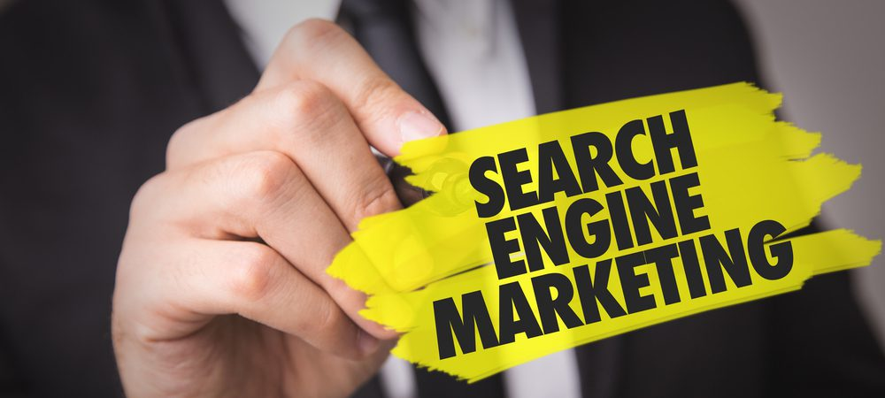 "A hand writing ""Search Engine Marketing"" on a screen."