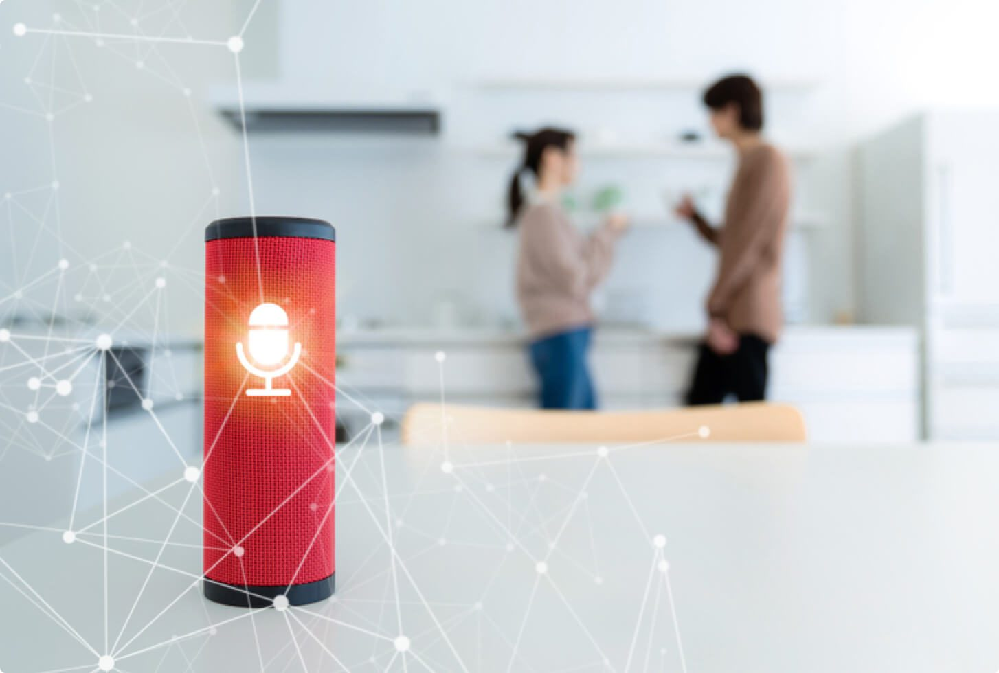 A red smart speaker shown in a kitchen with two people in the background