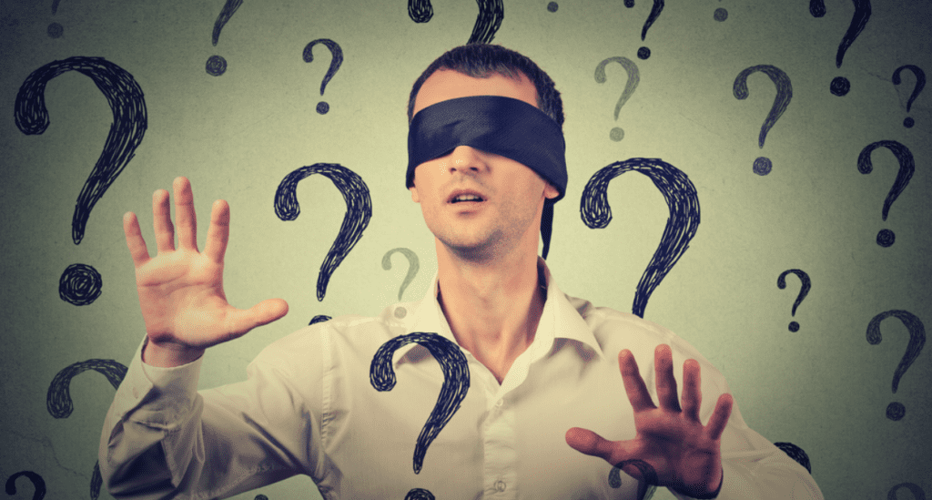 Blindfolded man surrounded by question marks.
