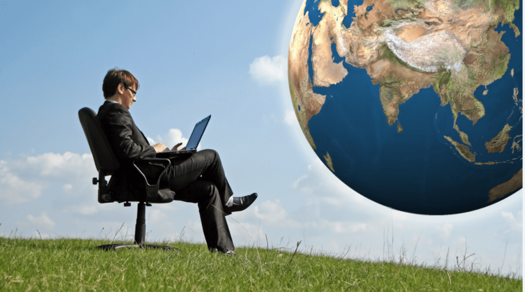 Person sitting outside with their laptop with a picture of the world in the distance.