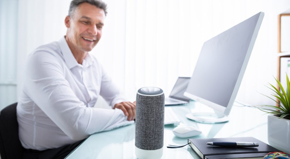 Man sitting in front of his computer and talking to his smart speaker