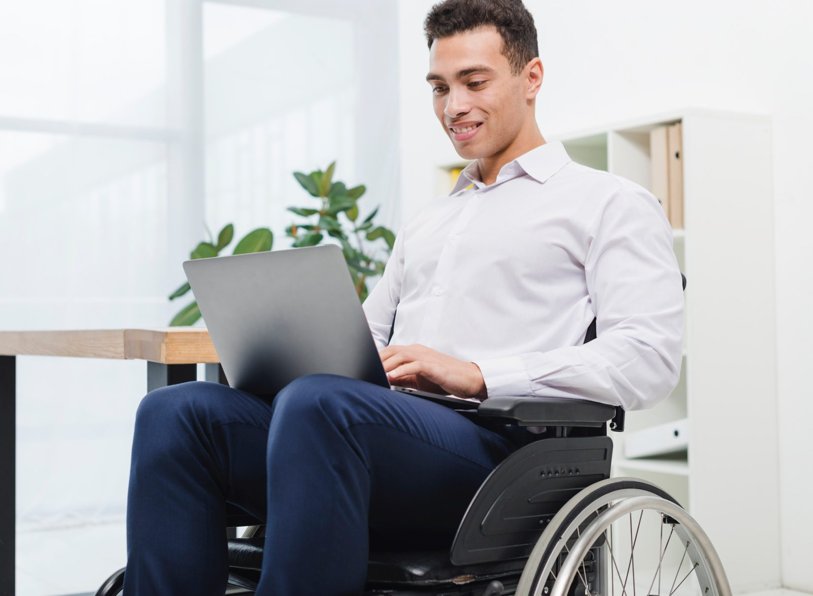 Man in a wheelchair looking at laptop on his lap and smiling.