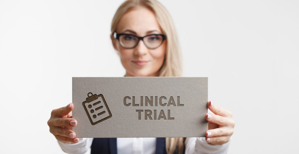 "Woman holding a paper sign that reads ""Clinical Trial"""