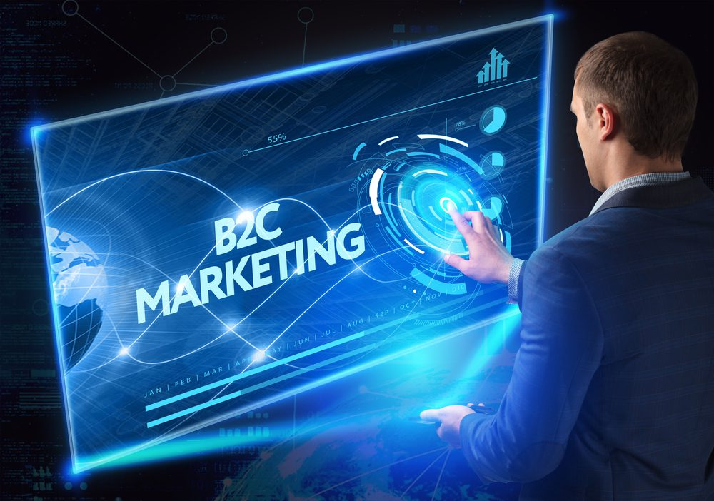 Business man interacting with a digital board displaying the words B2C Marketing