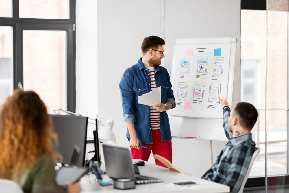 man showing user interface design on flip chart to creative team at office presentation
